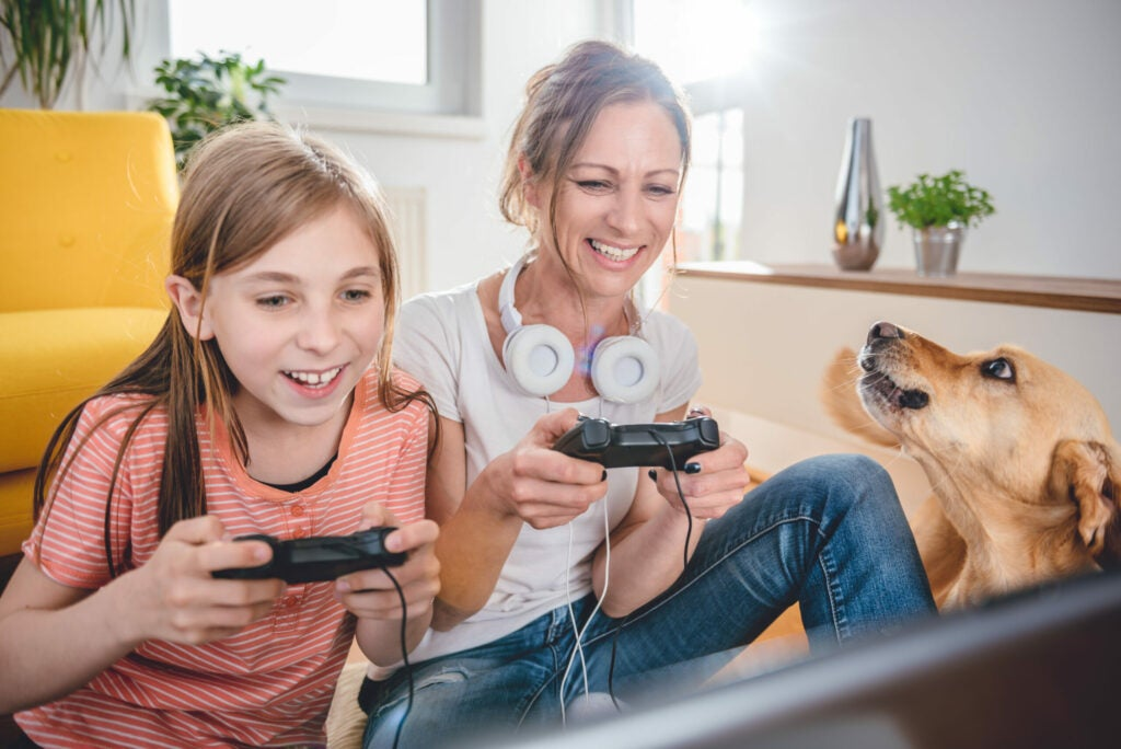 Mother and daughter playing video games on laptop at home