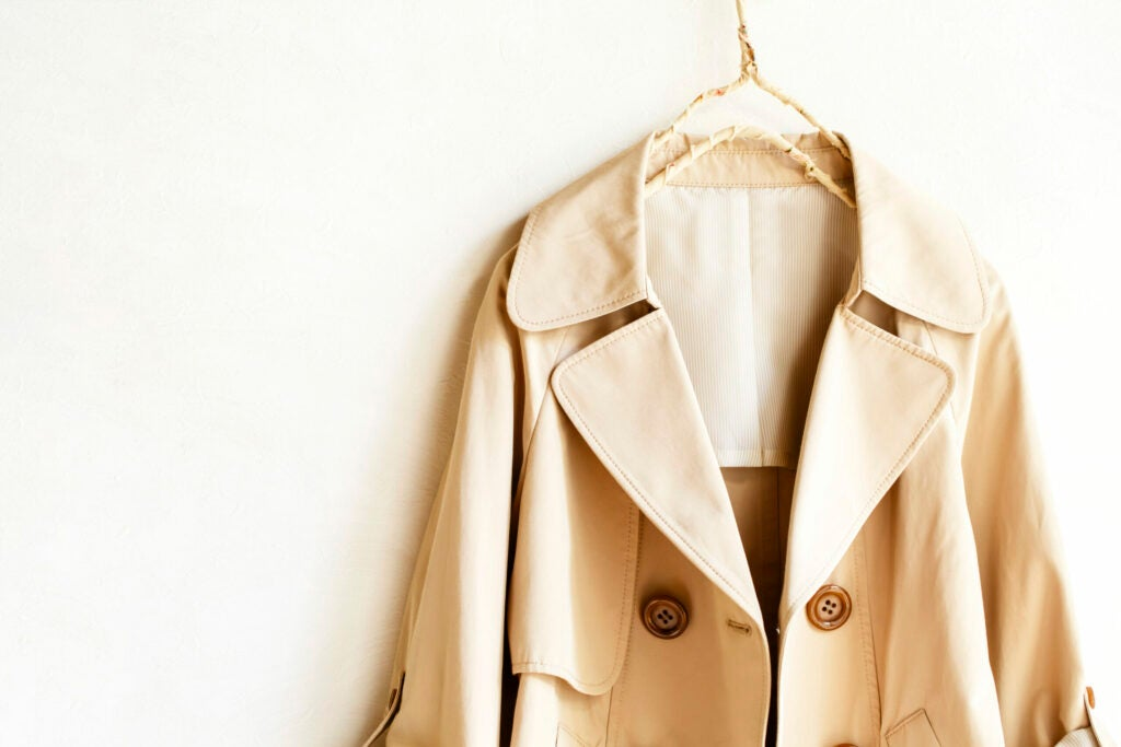 A beige elegant trench coat isolated over white. opened in front. Close up