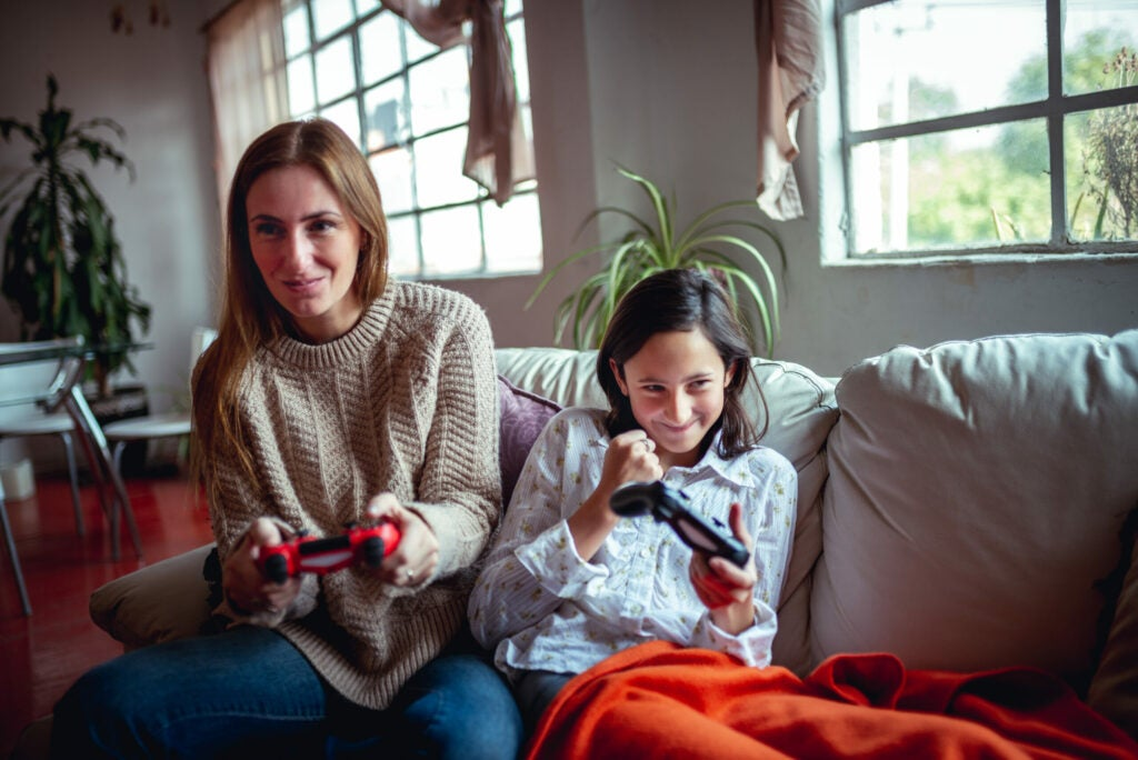 Mother and daughter are playing video games.