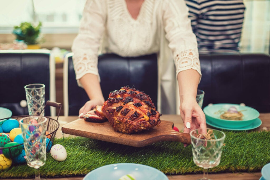 Family setting the table for traditional Easter lunch. Young woman bringing freshly baked holiday ham