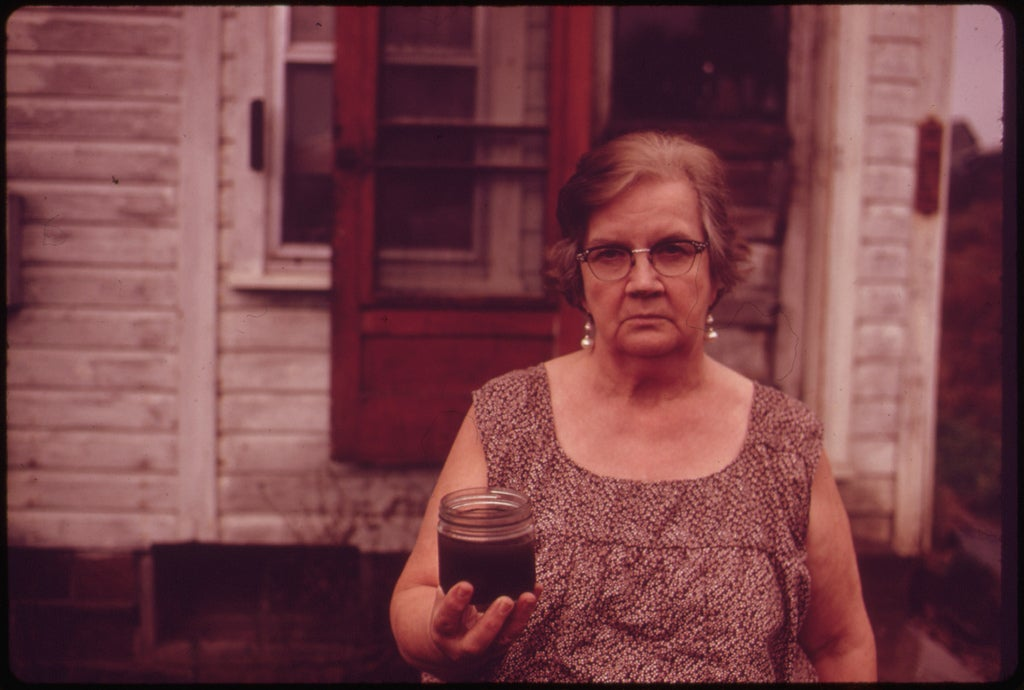woman holding jar of tainted water