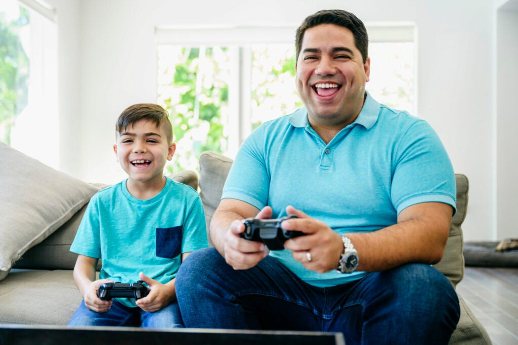 Laughing Latin American father and young son sitting on a sofa in the family home and playing video games.