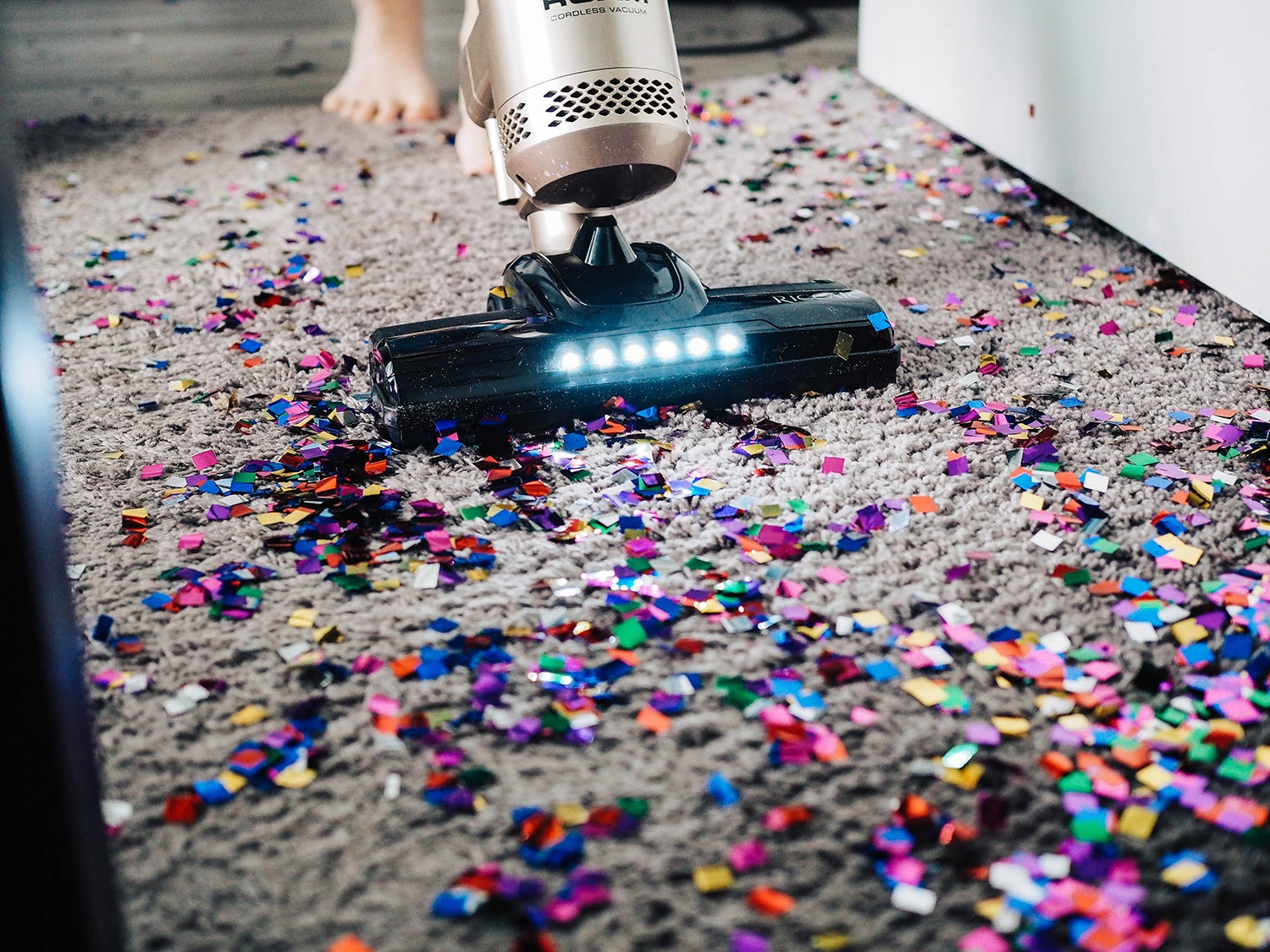 Cordless vacuum cleaning up confetti on the carpet