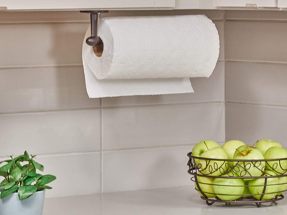 Paper towel holder above a counter with bowl of fruit