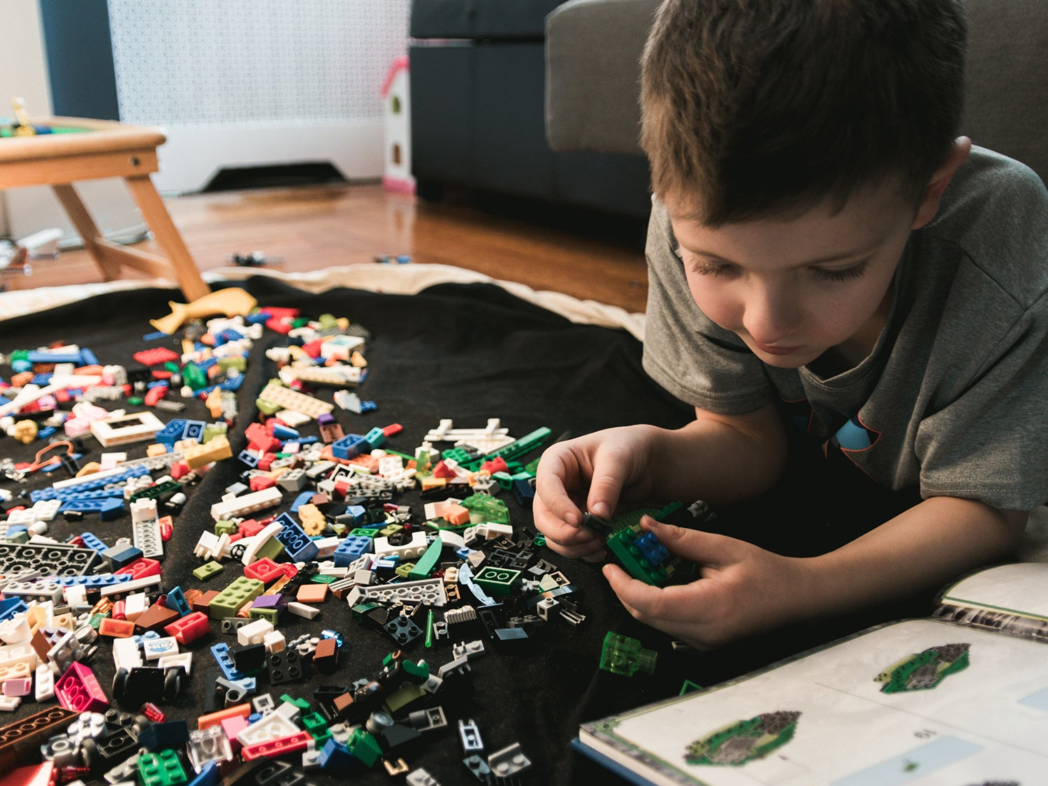 child on the floor playing with legos