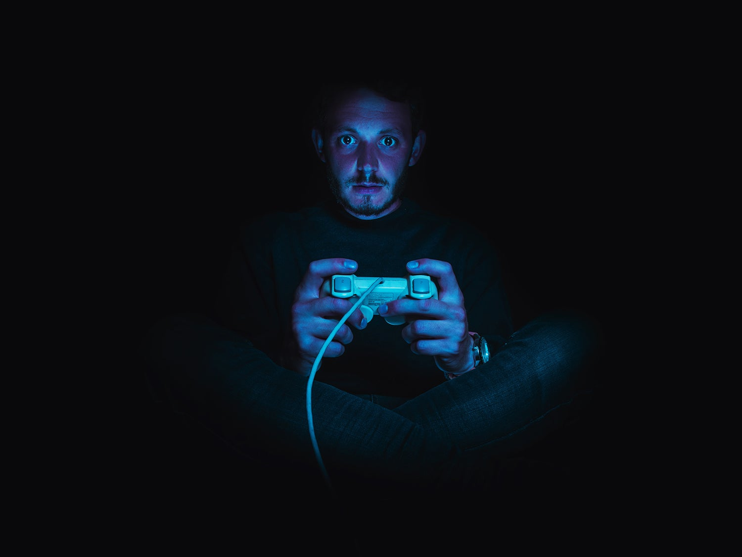 playing video games in the dark lit by tv