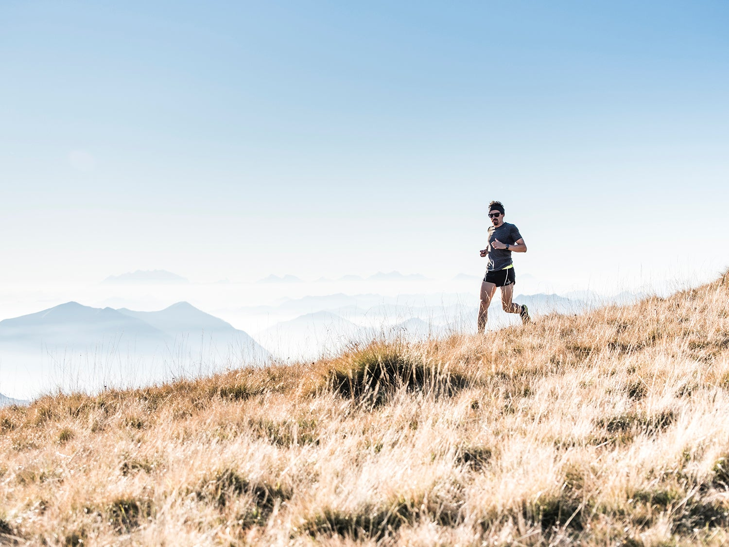 jogger on brown grass with mountains in the background