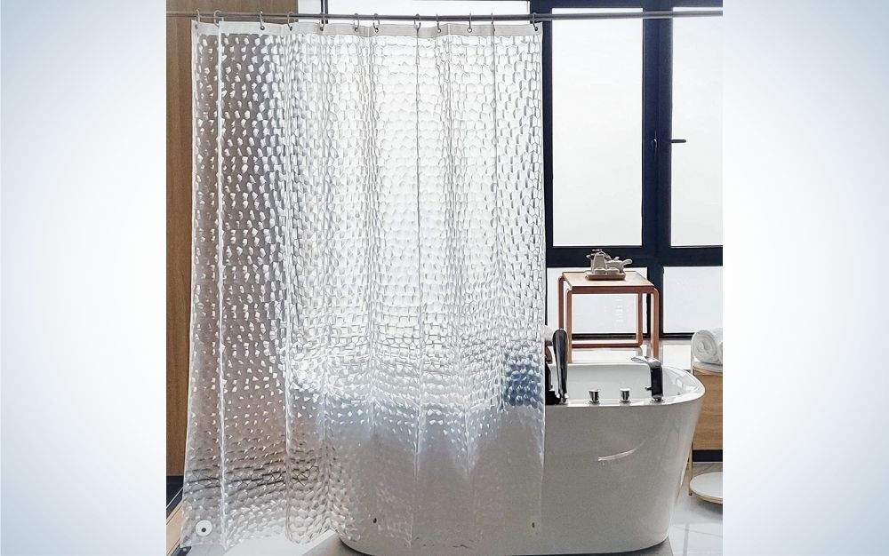 A white and almost translucent shower curtain in the form of glass and behind it a modern oval bath and a modern bathroom.