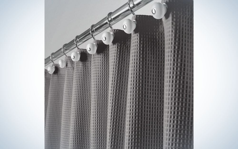 A shower curtain hanging on aluminum all in dark gray.
