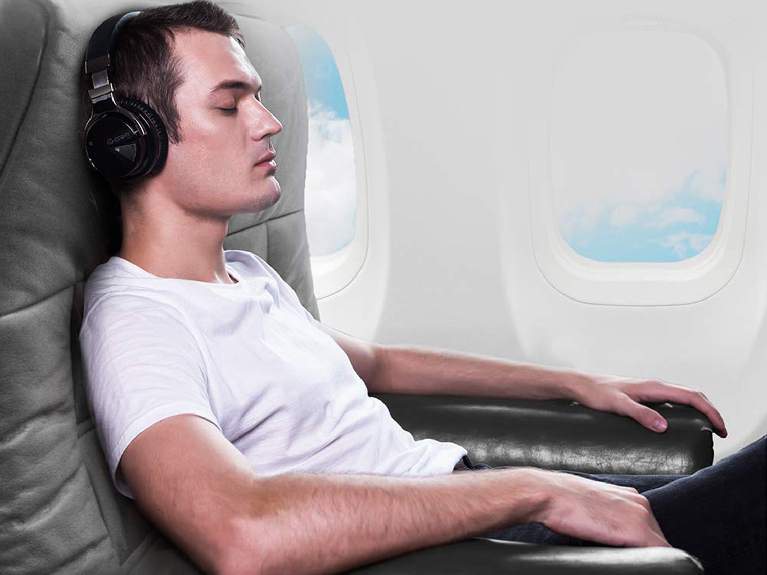 Man wearing noise-cancelling headphones on a plane.