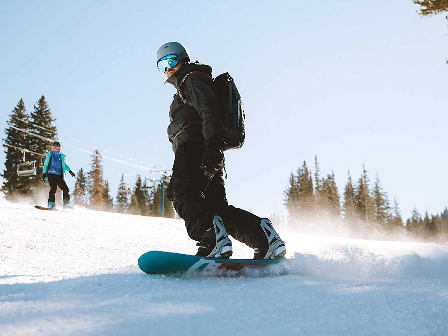 Snowboarder boarding down mountain.