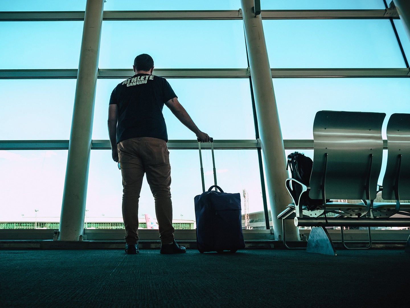 Man holding rolling suitcase at the airport