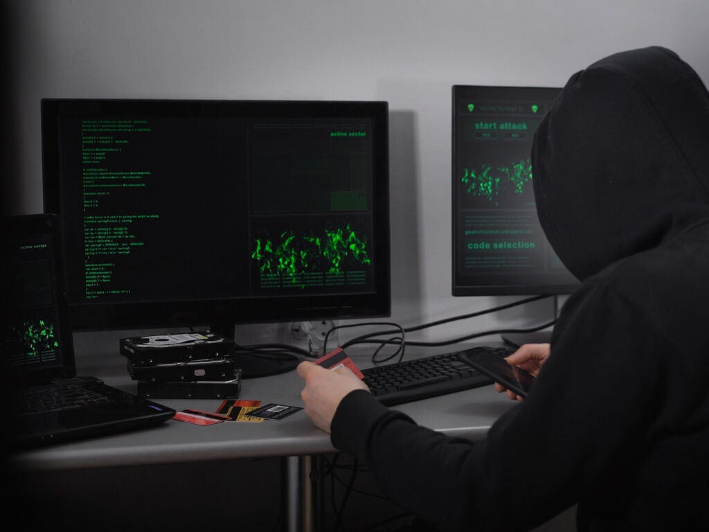 hooded man stealing credit card information