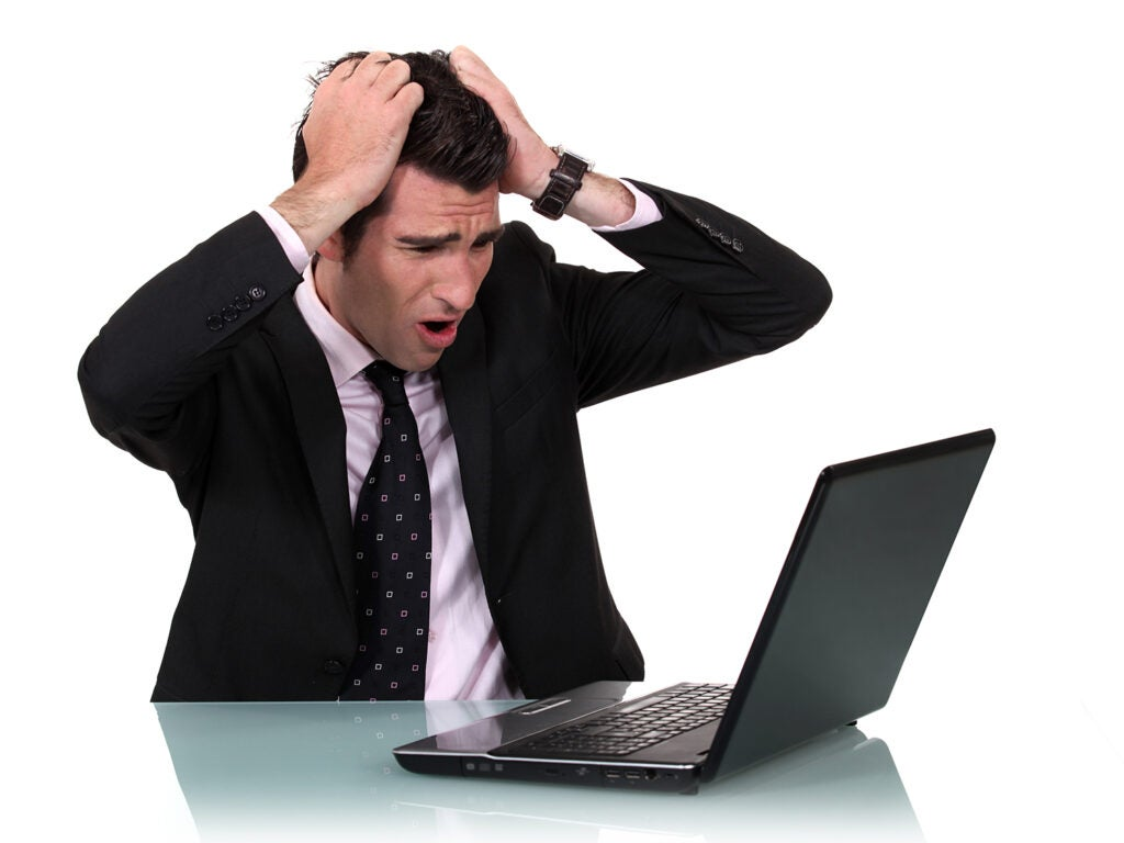 business man with hands on head in worry