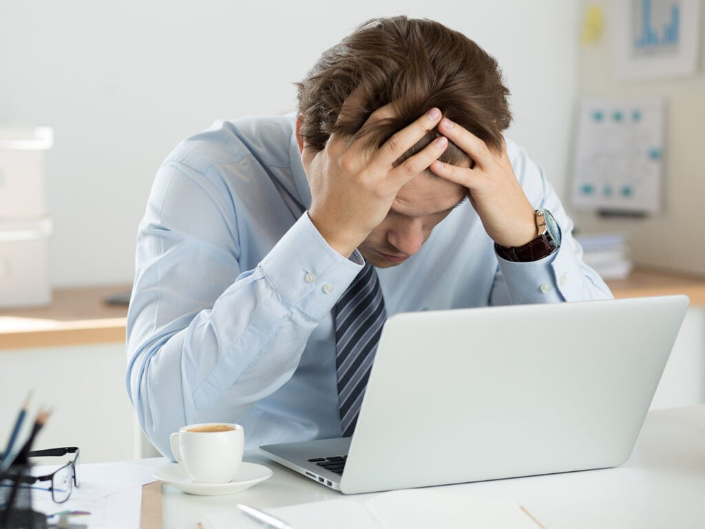 business man with head in hands over laptop