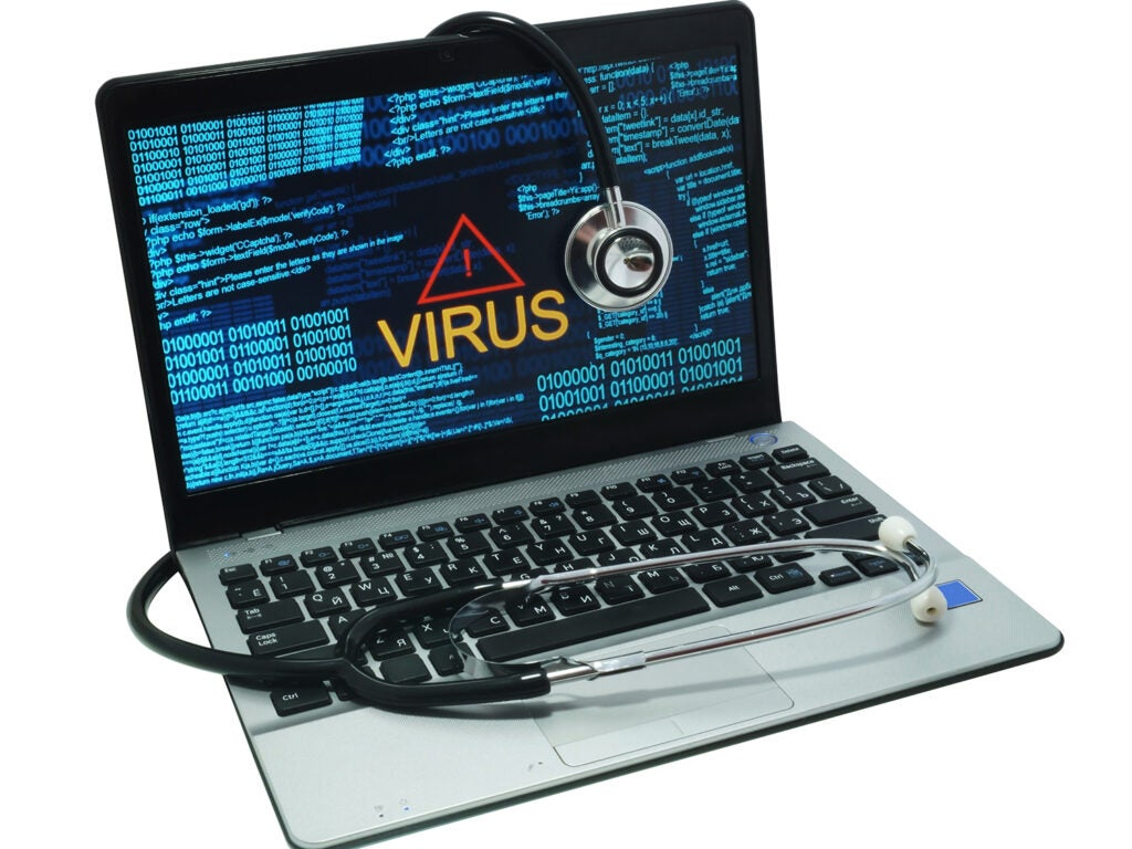 stethoscope draped on a laptop with a virus