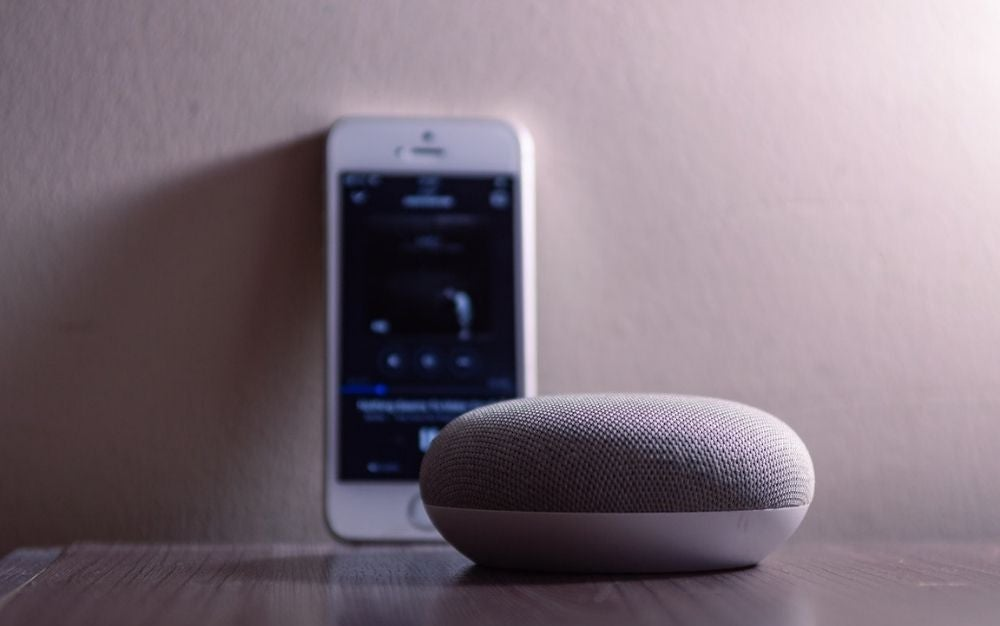 A grey and circle form speakers in front of the smartphone over the wooden table.