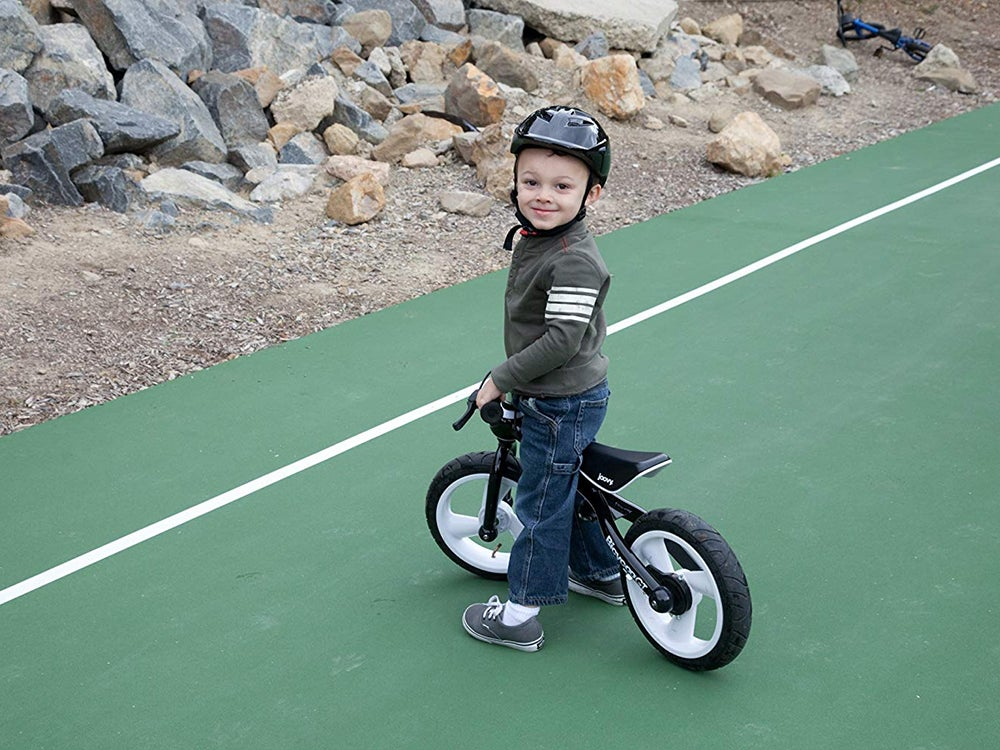 small kid on a bicycle with a helmet