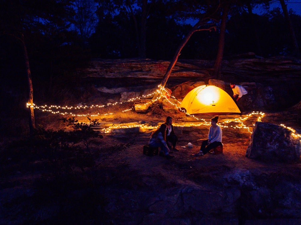 Camping at night with string lights