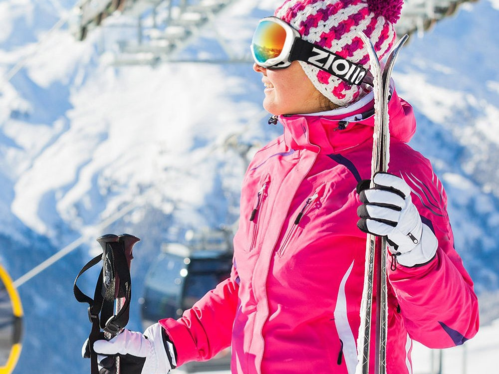 Woman in pink snow jacket with skiis