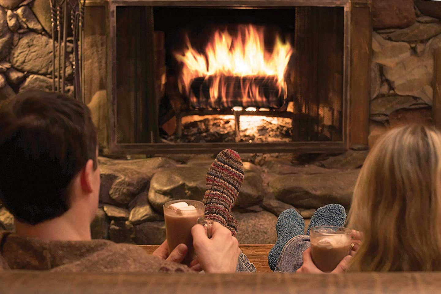 Couple sitting by a fire.
