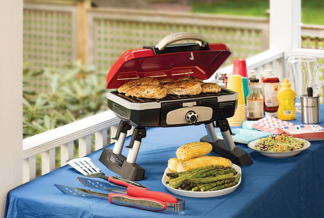 Portable gas grill on a picnic table.