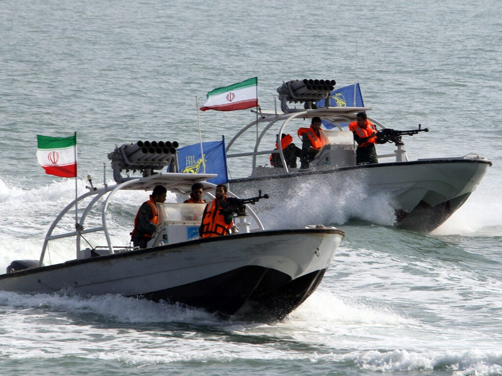 Iranian Revolutionary Guards drive speedboats during a ceremony