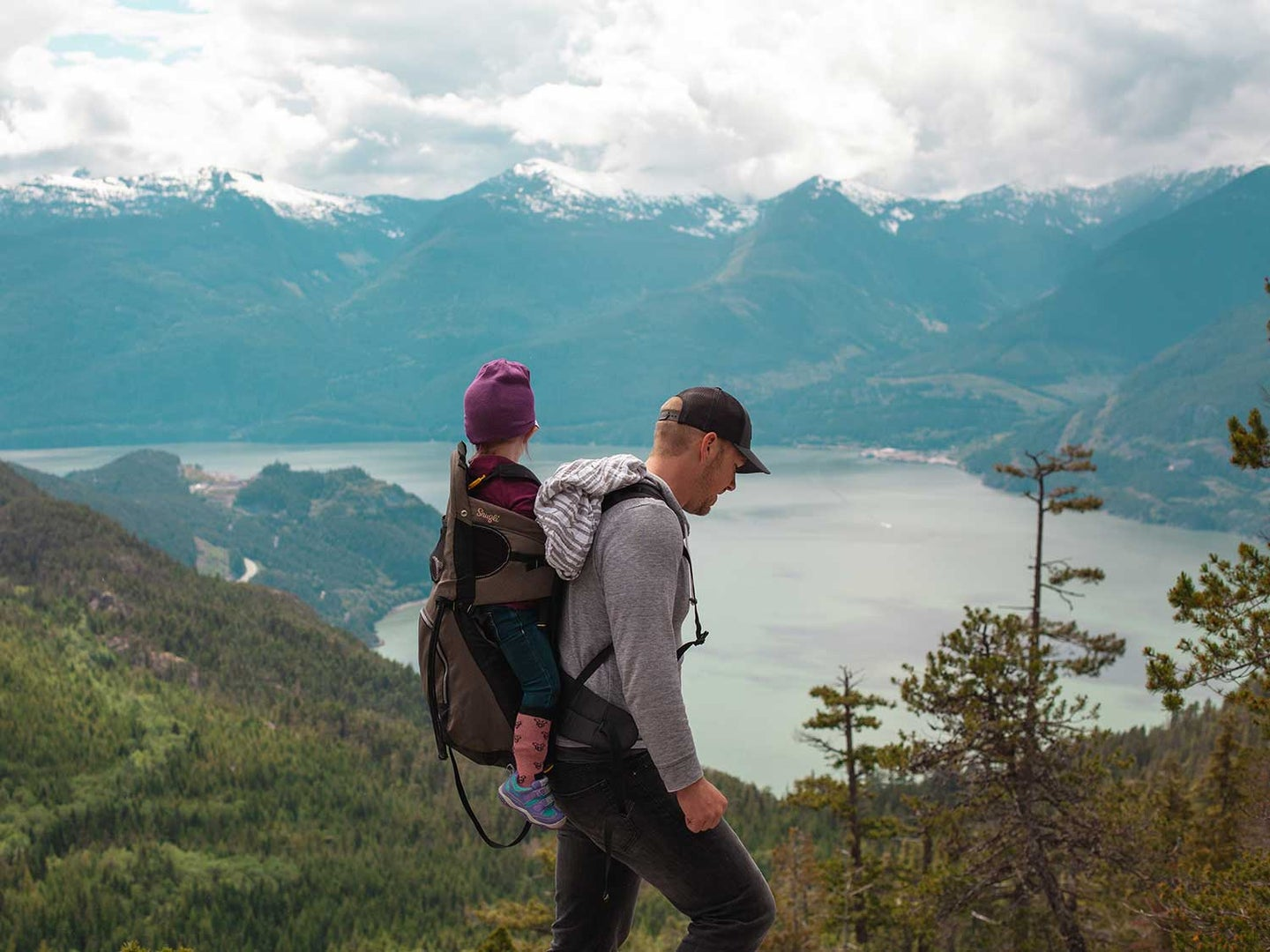 Dad hikes with kid in the mountains.