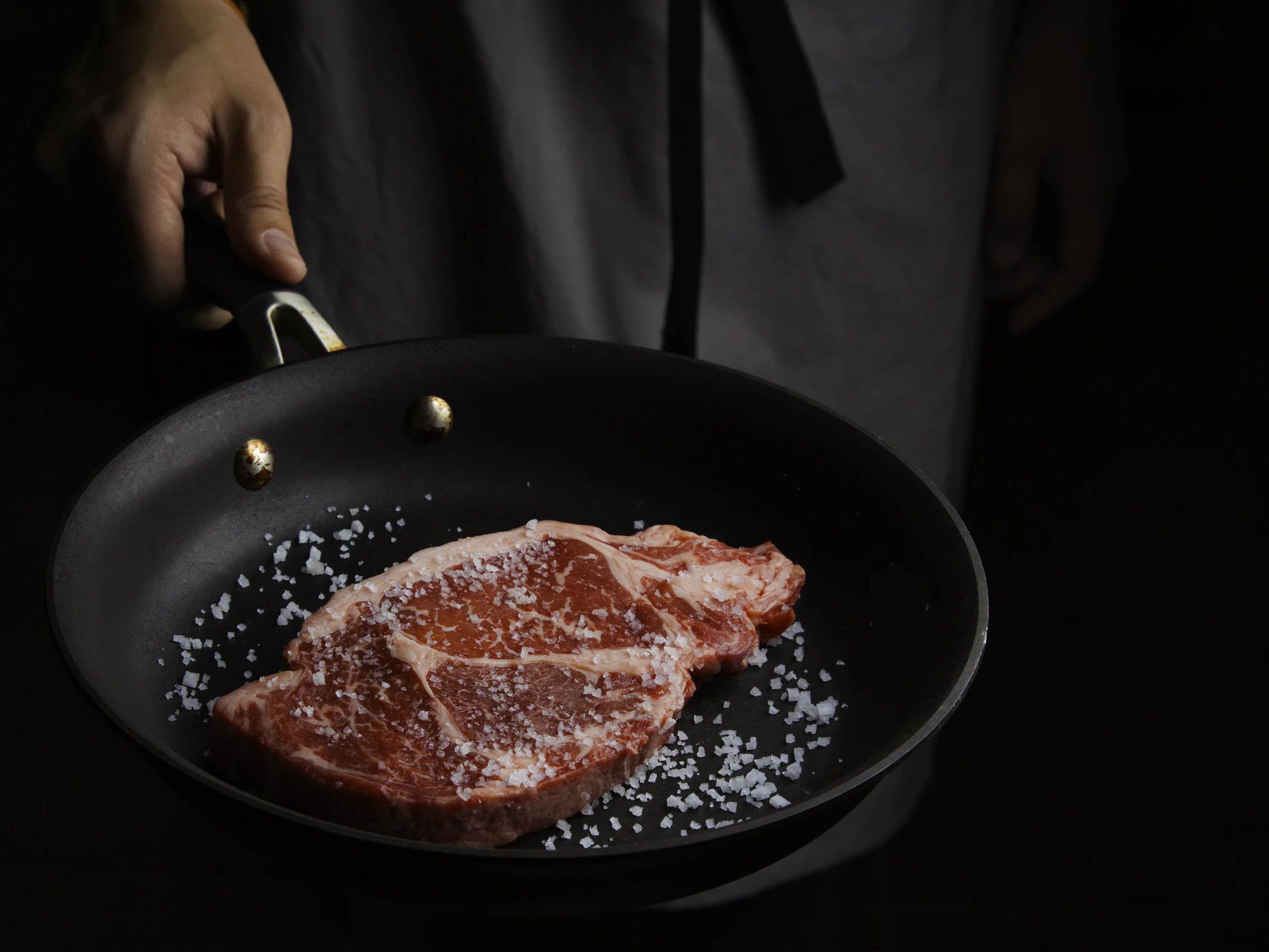 Person cooking steaks in a non-stick pan