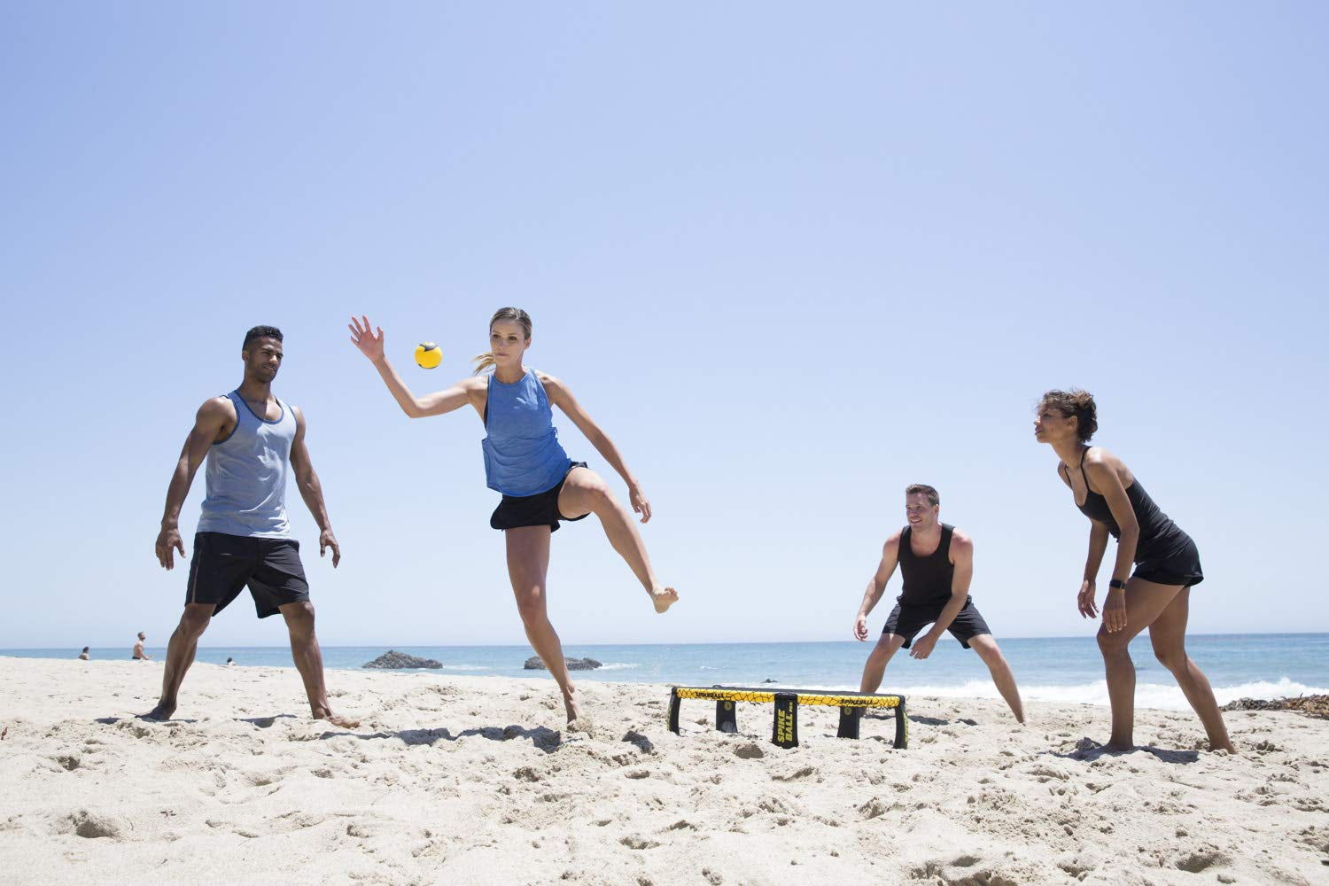 People playing Spikeball on the beach