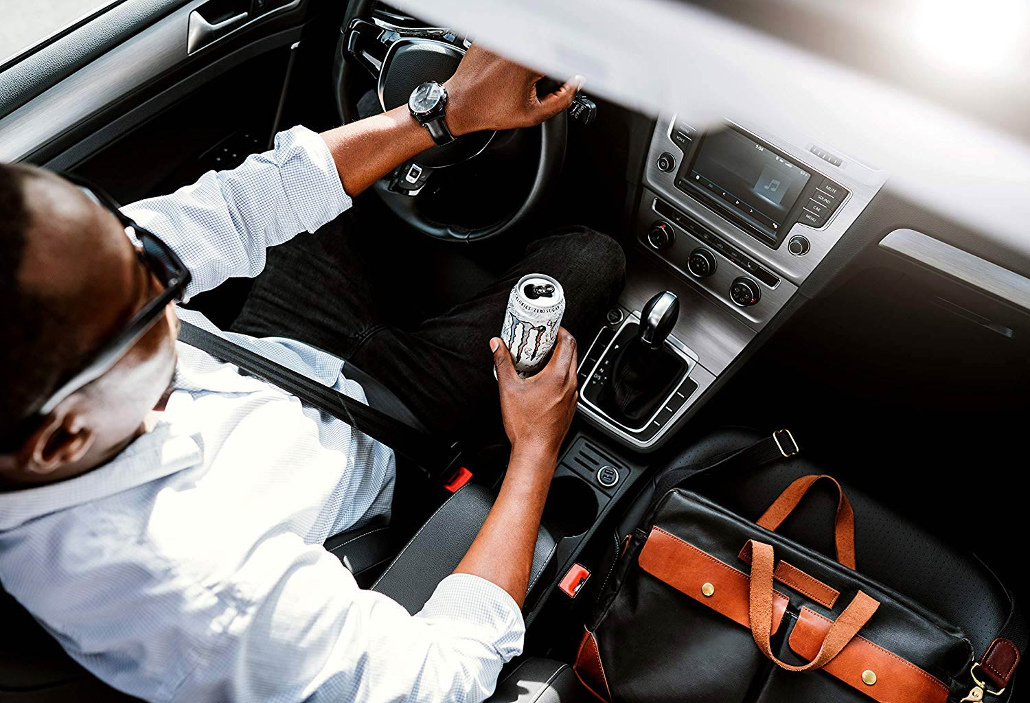 Man driving a car while drinking an energy drink
