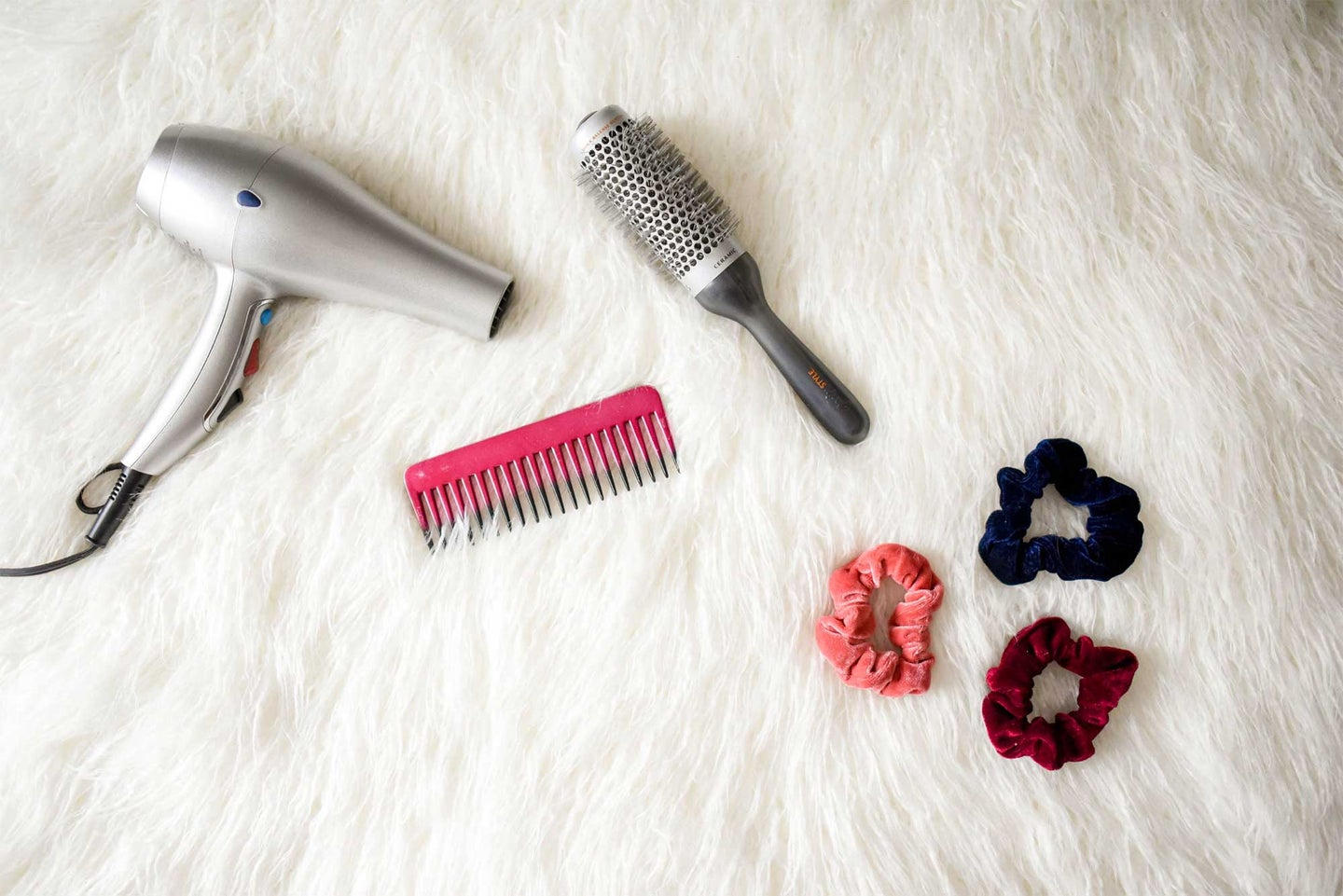Hair dryer and scrunchies on a fur carpet