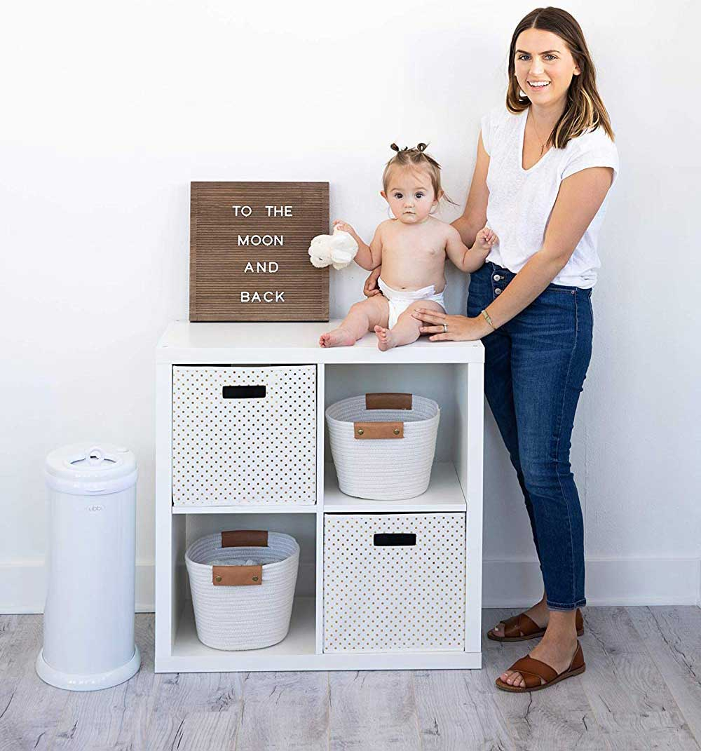 Mom and baby with diaper disposal trashcan.