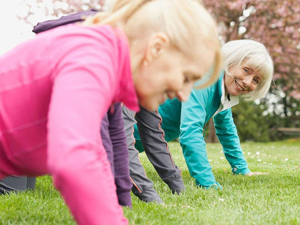 Two women exercise at the park.