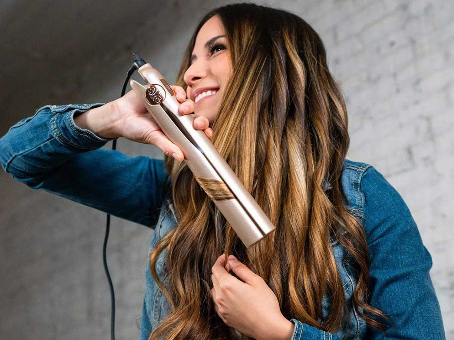 Woman curling hair with curling iron