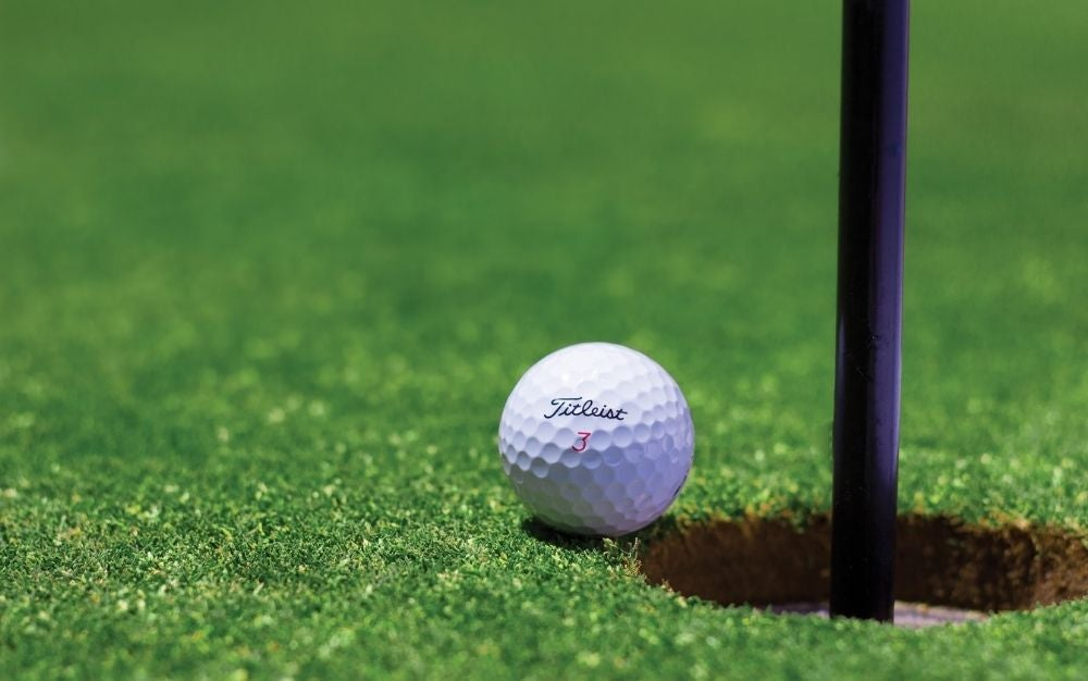 A white golf ball on the side of the pit to be inserted into a piece of green grass.