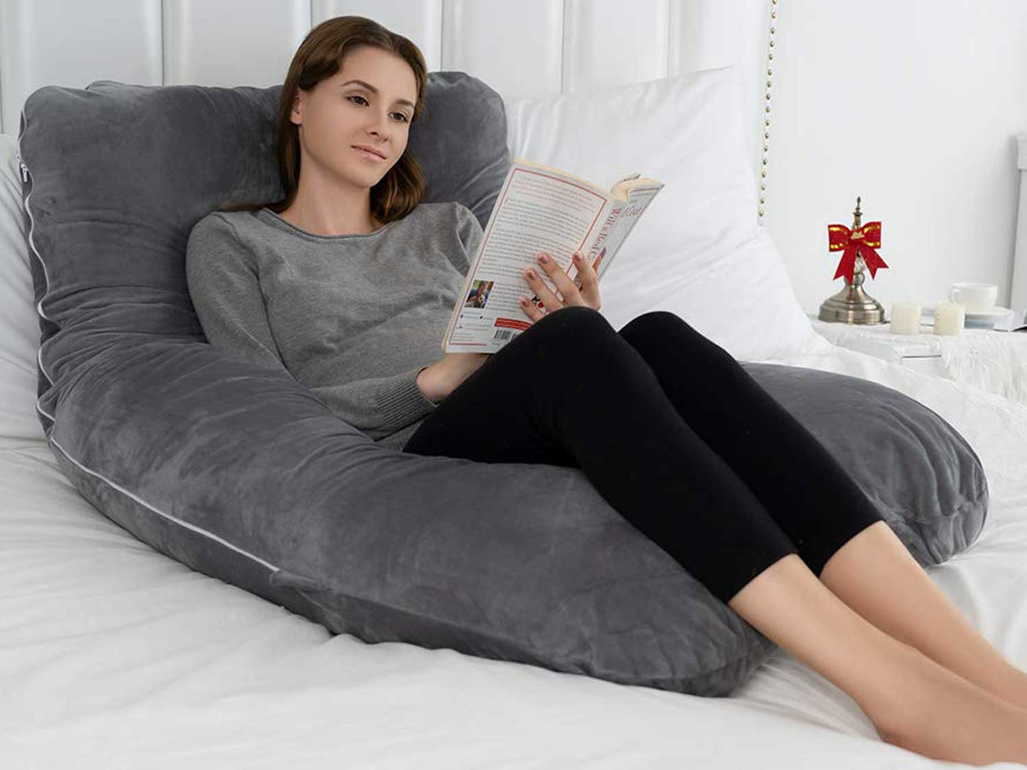 Woman reads and sits on body pillow.