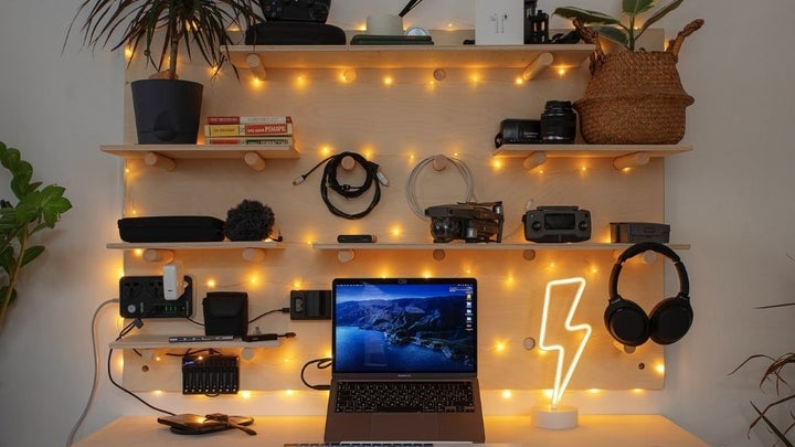 A lighted laptop which stands in the middle of a room, a wall made of light and with some wooden shelves where some technological accessories are lined up.
