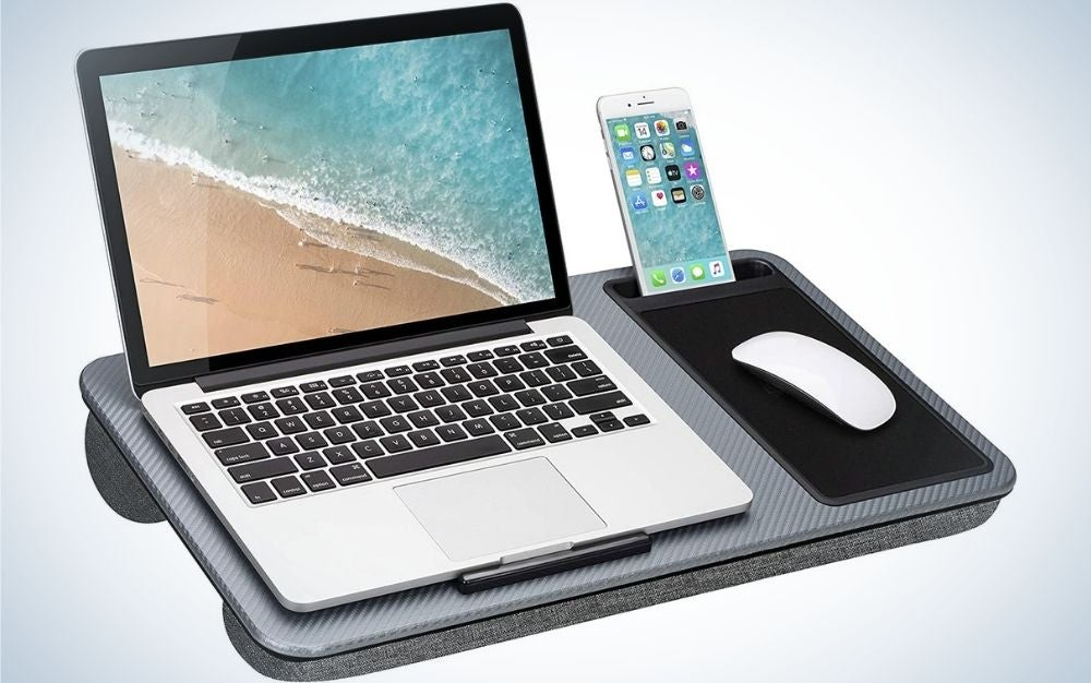 A laptop turned on and open and next to it a lighted smartphone which stand positioned on a laptop holder and gray phone.