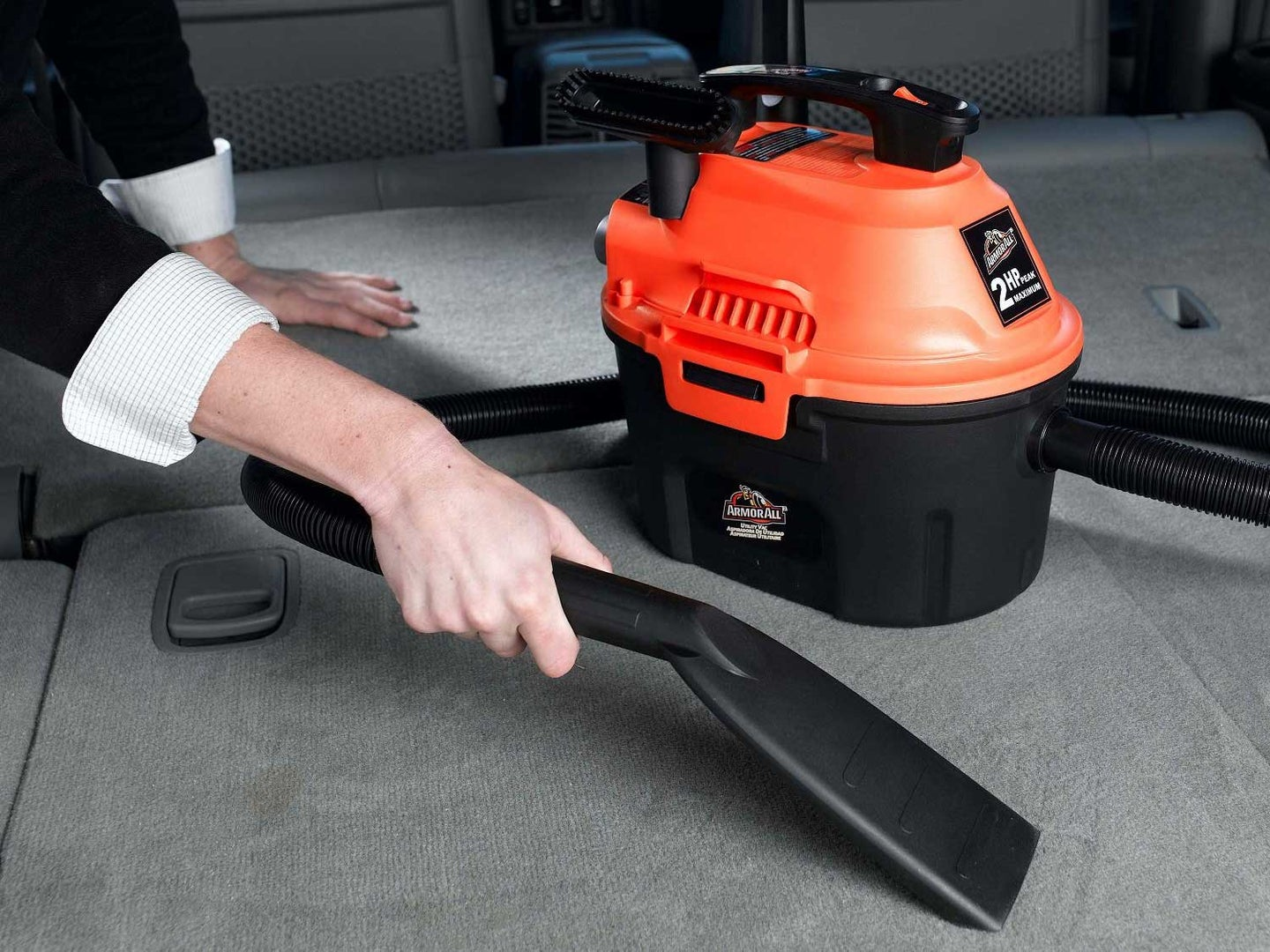 Vacuuming the inside of a car with a portable vacuum.