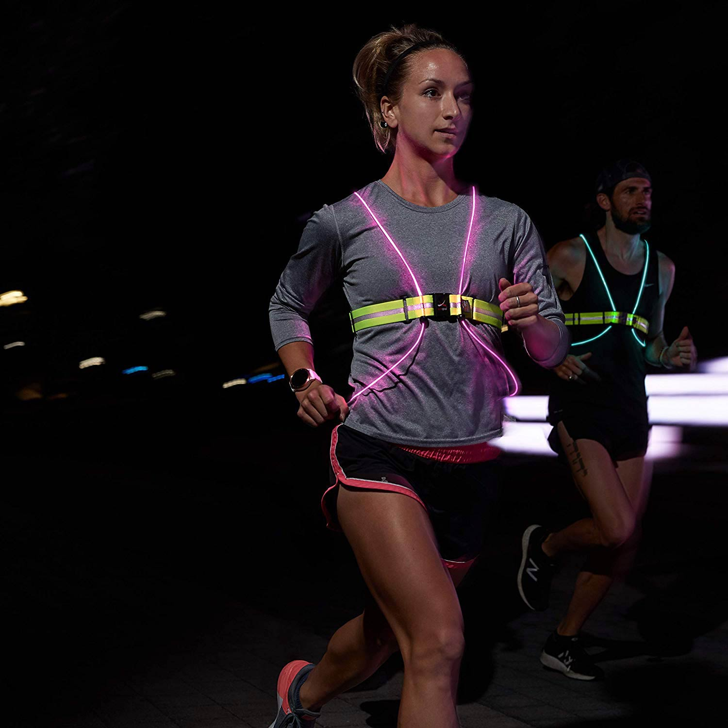 Women running at night with neon reflective vest