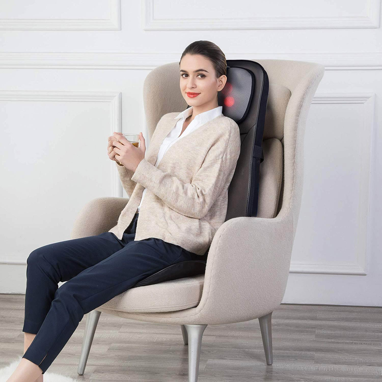 Woman sitting in chair with back massager