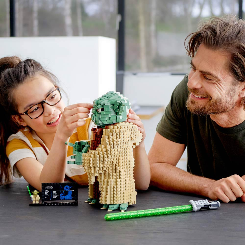 Child with dad putting a baby Yoda LEGO together