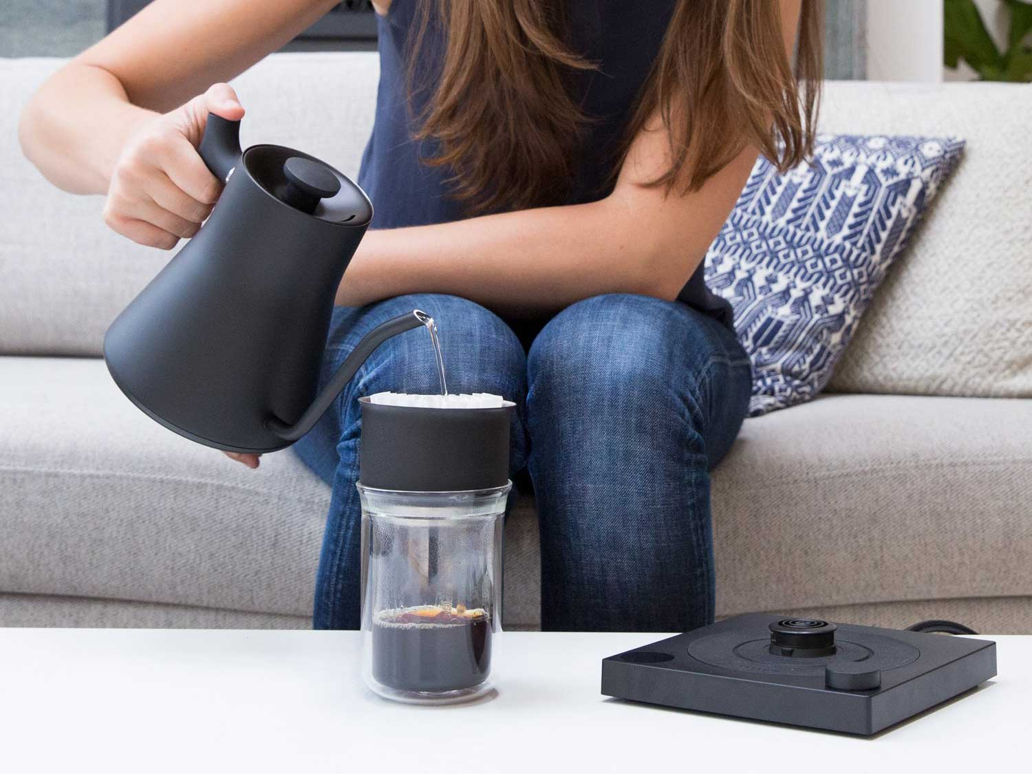 Pouring hot water out of electric kettle over coffee