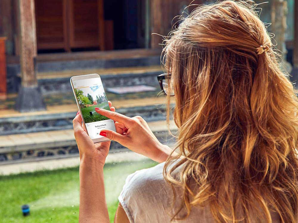 Woman controls sprinkler system on phone