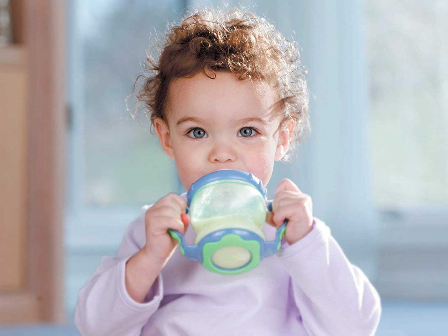 Baby drinking formula out of sippy cup