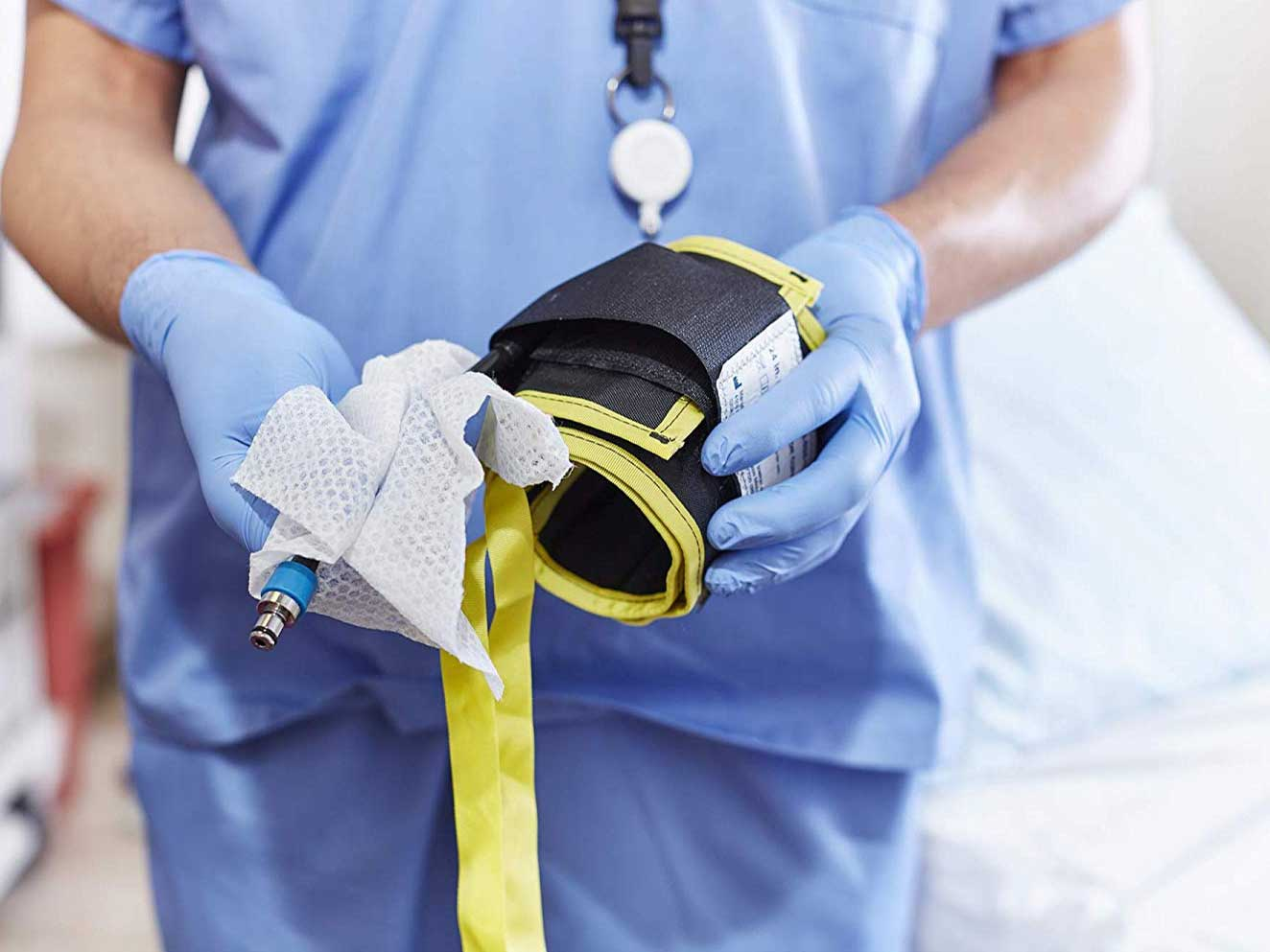 Nurse wipes down a blood pressure cuff with disinfecting wipes.