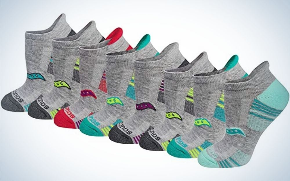 Multiple pair of grey socks with colorful designed ones with different color for each sock.