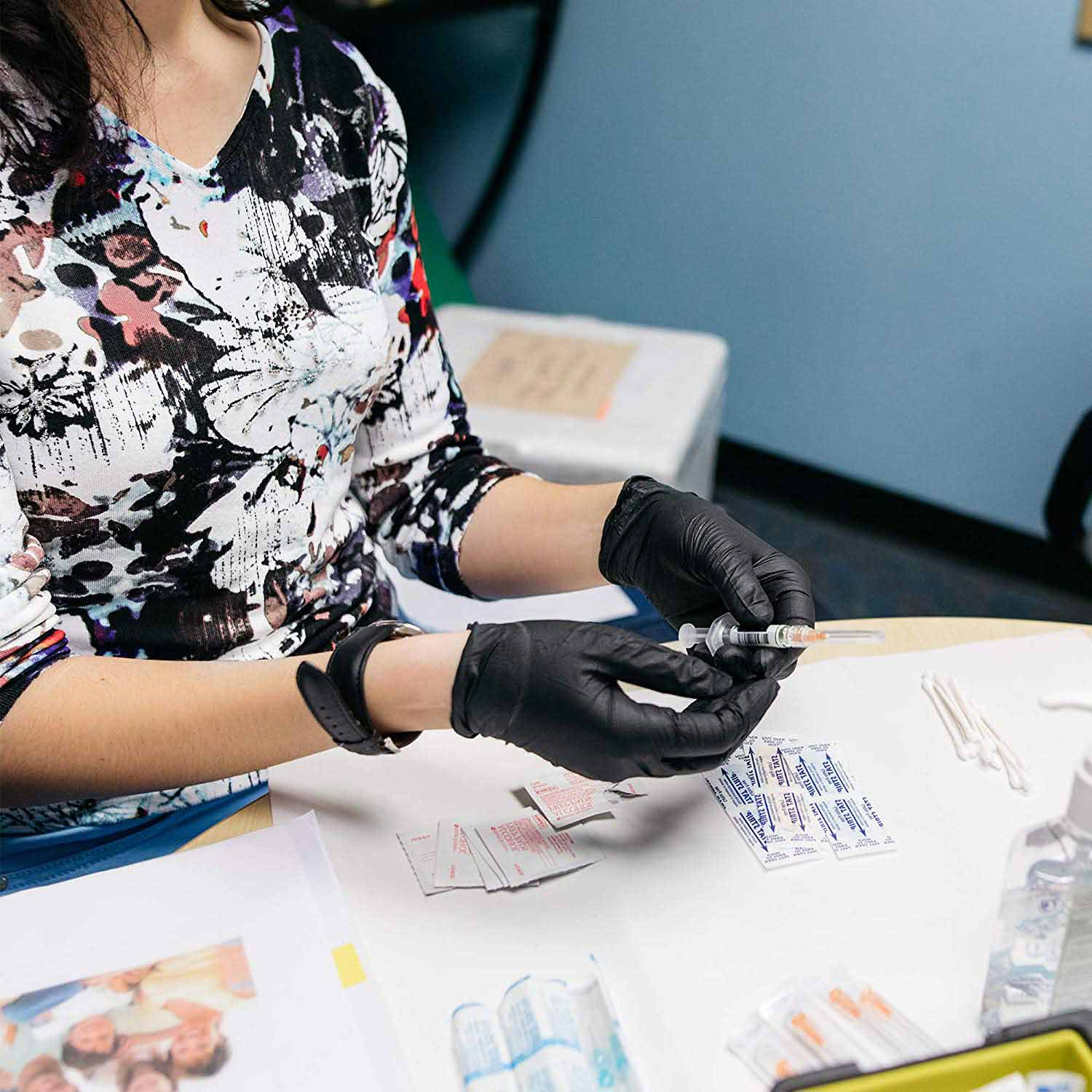 Woman wearing latex gloves holding a needle
