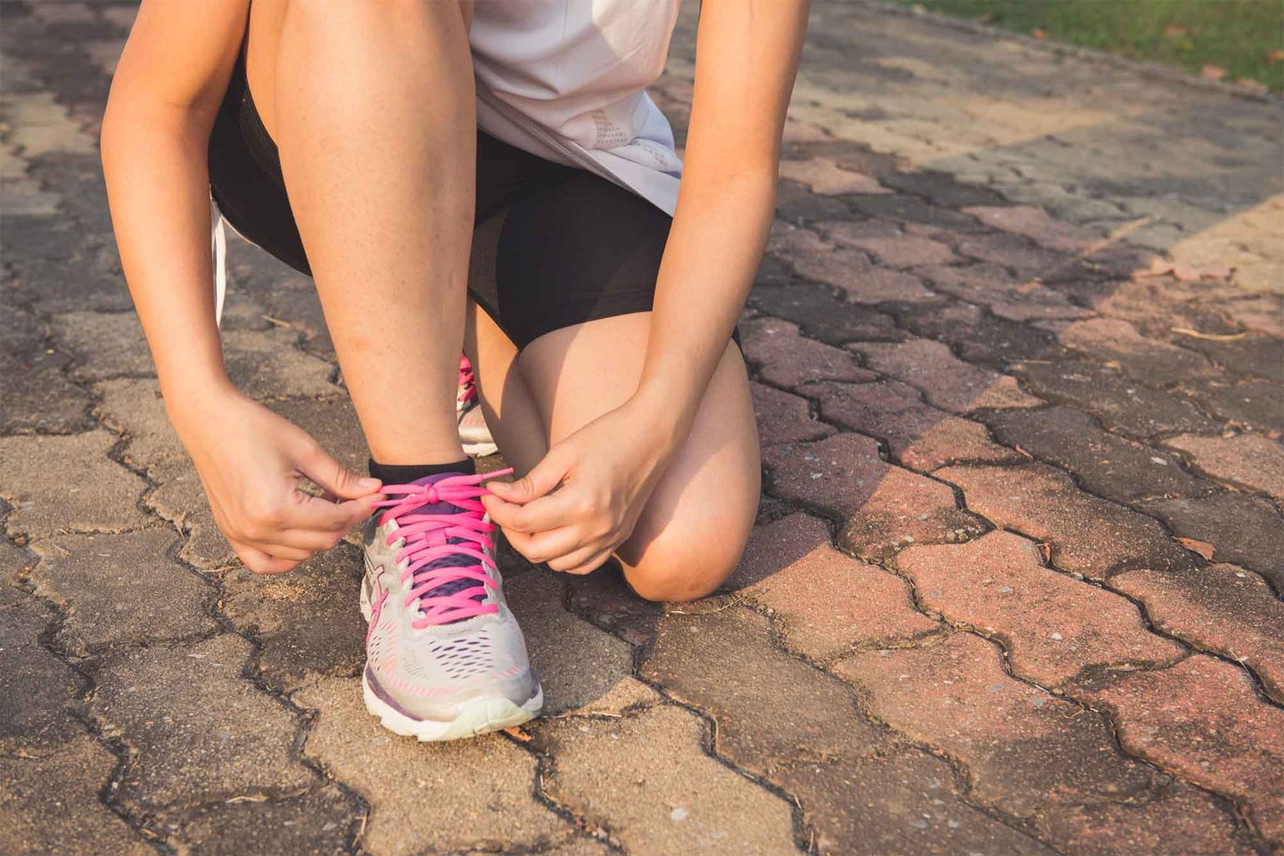 Woman lacing up her running shoes.